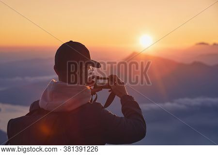 Young Man On Top Of Mountain Photographing Sun Under Horizon. Lucerne, Switzerland.
