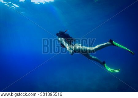 A Young Woman Is Diving In Cristal Water With Mask  And Fins