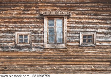Wall Of An Old Farm Building. Natural Wooden Texture, Rural House For Agritourism, Different Windows