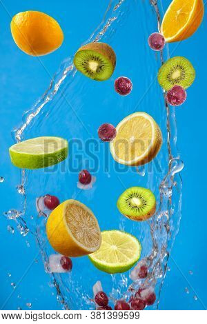 Falling Fresh Mixed Fruits. Slices Of The Lemon, Orange, Lime, Kiwi And Cherry With Fresh Water In T