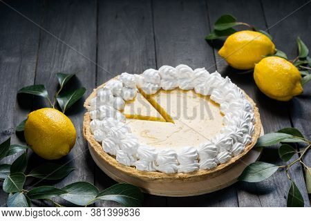 Homemade Lemon Pie With Meringue, Cutted Piece, With Fresh Lemons On Black Wooden Background, Select