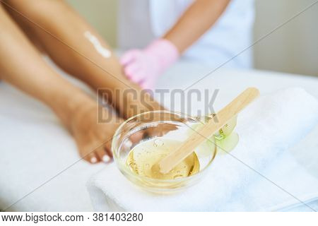 Cosmetologist Is Doing Depilation. The Procedures At The Beautician. A Jar Of Wax In The Foreground.