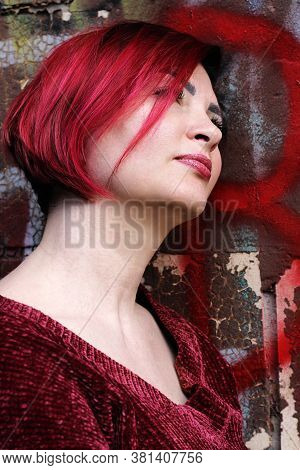 Portrait Of Beautiful Woman With Bright Red Hair Outdoors, On Grafiti Background