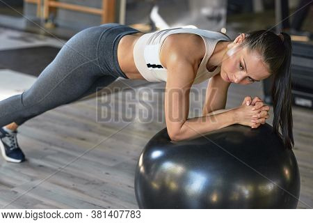 Horizontal Image Of Athlete Woman Doing Exercises With Fit Ball At The Gym. Caucasian Gumnastic Girl