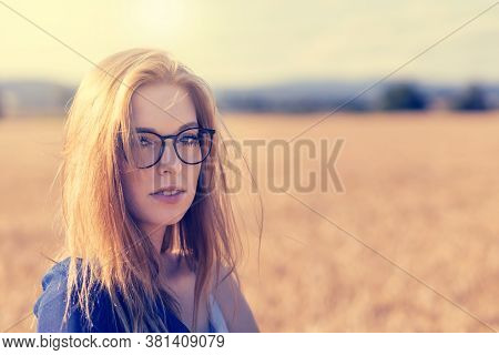 Young Woman With Glassesis Is Posing In Backlight Outdoors. Edited As A Vintage Photo.