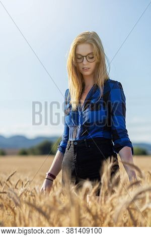 Portrait Of Young Woman With Glasses Wearing A Blue Plaid Shirt Is Posing In Backlight Outdoors. Ver