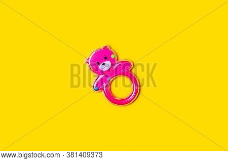 Pink Baby Rattle On Yellow Background Isolation, Top View