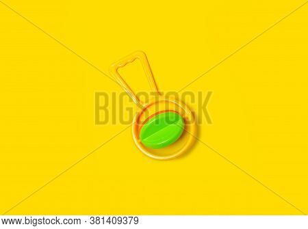 Yellow Baby Rattle On Yellow Background Isolation, Top View