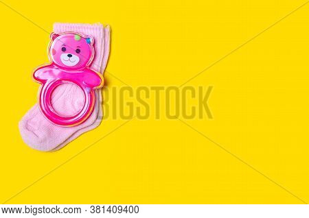 Pink Baby Rattle With Pink Socks On Yellow Background Isolation, Top View