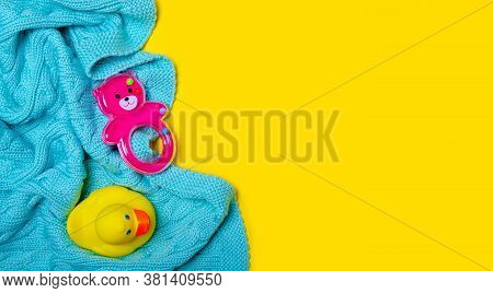 Pink Baby Rattle, Baby Knitted Plaid On Yellow Background Isolation, Top View