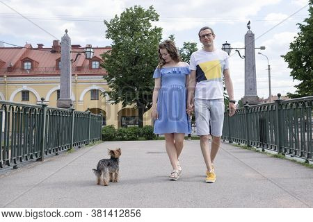 White Man Walks Down The Street With A Pregnant White Woman And A Dog,  Family On A Walk