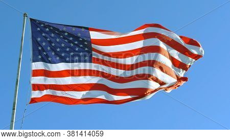 American Flag Blowing In The Wind With A Blue Sky, Usa American Flag. Waving United States Of Americ
