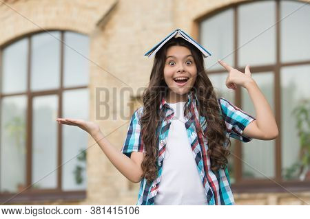 Bestselling Product. Happy Kid Hold Open Hand Pointing At Book On Head. Little Girl Presenting Produ