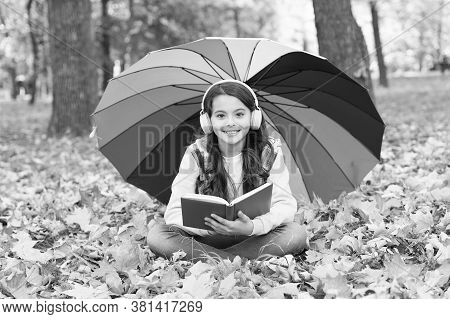 Audio Learning In Any Weather. Small Girl Listen To Audio Book On Autumn Landscape. Little Child Enj