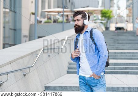 Travel Free With Technology. Bearded Man Listen To Music Urban Outdoors. Hipster Wear Headphones In