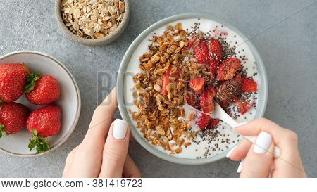 Eating Granola With Strawberries And Yogurt. Female Hands Holding Bowl Of Homemade Honey Oat Granola