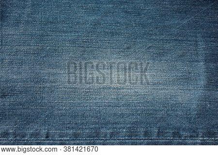 Fragment Of Blue Frayed Denim Jeans Background