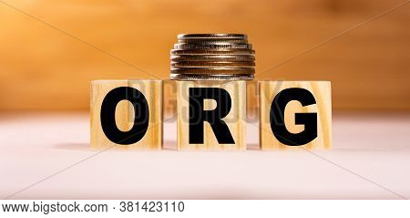 The Concept Of The Word Org On Wooden Cubes With Coins On A White Wooden Background. Business Concep