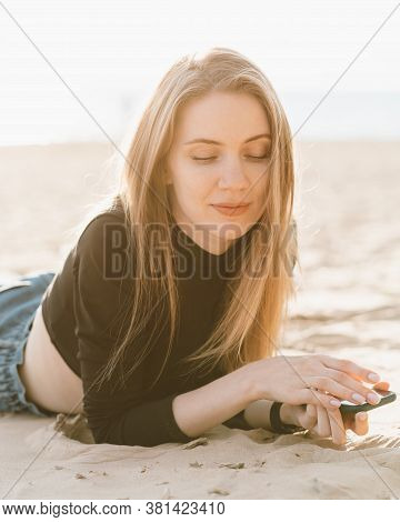 Young Beautiful Woman With Long Hair Is Relaxing On Sandy Beach With Mobile Phone In Backlight.