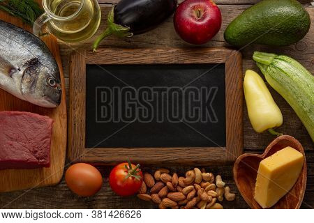 Keto diet low carbs food. Healthy products. Diet concept. Vegetables, fish, meat, nuts, seeds, tomato, apple, cheese on a brown background. Top view.