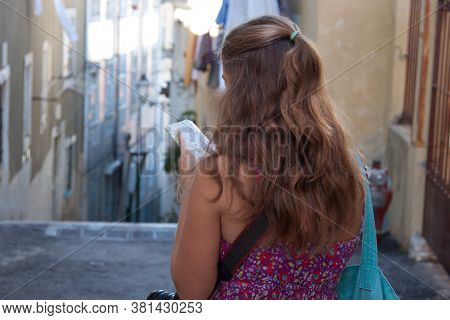 Backview Of Young Woman With Long Hair Watching Touristic Map In The City Center Of Old Town