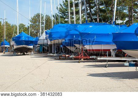 Protective Blue Tarp On Boats In Michigan Outdoor Storage Lot