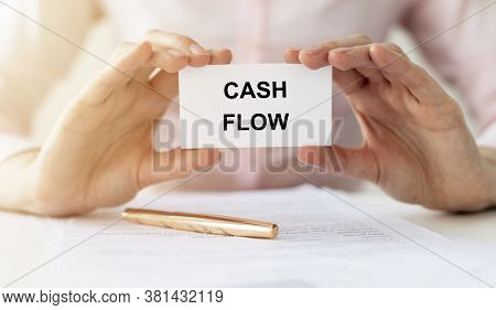 Female Hands Holding White Card Note Written Cash Flow Word At Office Table
