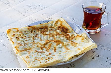 Traditional Turkish Food Flatbread, Gozleme, Near Cup Of Turkish Tea, Dough Bread With Cheese Cooked