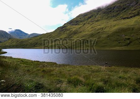 Scottish Mountains And Small Loch At Dusk In Summer.