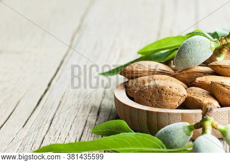 Almond Nuts, Almonds With Shell In Bamboo Bowl On Wooden Background With Green Fresh Raw Almonds On