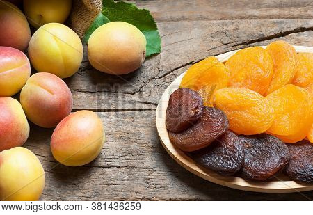 Natural Dried Apricots In Bamboo Bowl With Fresh Whole Ripe Apricot On Wooden Rustic Backdrop, Dry A