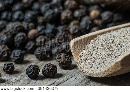 Heap Of Black Pepper And Black Pepper Powder In Wooden Spoon, Milled Peppercorns On Wooden Backgroun