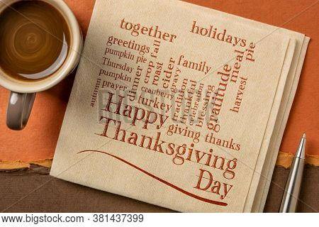 Happy Thanksgiving Day word cloud - handwriting on a napkin with a cup of coffee against handmade paper in brown and orange tones