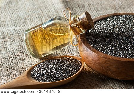 Glass Bottle Of Chia Oil And Chia Seeds ( Salvia Hispanica ) In Wooden Spoon Or Bowl On Rustic Backd