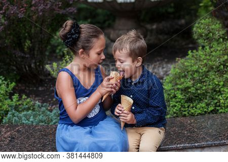 Brother Give His Icecream To Sister. Eating Icecream In Park