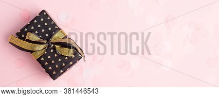 Gift Or Present Box With Gold Bow And Gold Heart, Confetti On Pink Pastel Table Top View. Compositio