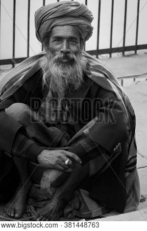 Black And White Street Portrait Of An Old Hindu Sadhu With White Beard, Sitting And Smiling Towards