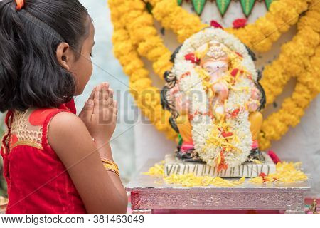 Girl Kid Praying By Closing Eyes And Folding Hands In Front Of Lord Ganesha Idol During Ganesha Or V