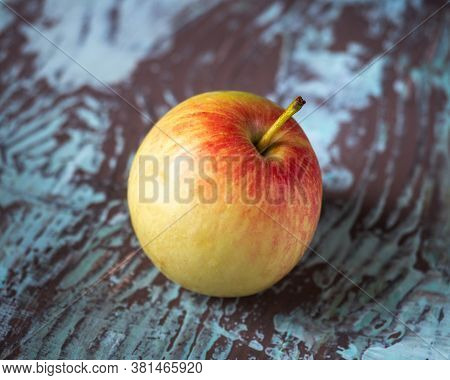 Single Yellow-red Apple On Motley Wooden Background