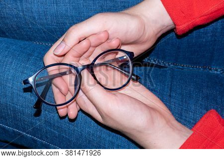 Close-up Of Human Hands Holding Blue Rimmed Glasses On Their Knees. Eyes Rest From Glasses. Glasses