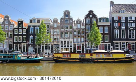 Amsterdam, Netherlands - Mai 29, 2020: Crooked Heritage Buildings And Colorful Barges, Located Along