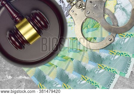 1 Romanian Leu Bills And Judge Hammer With Police Handcuffs On Court Desk. Concept Of Judicial Trial