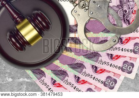 20 Sri Lankan Rupees Bills And Judge Hammer With Police Handcuffs On Court Desk. Concept Of Judicial