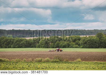 Tractor Plowing Field In Spring Season. Beginning Of Agricultural Spring Season. Cultivator Pulled B