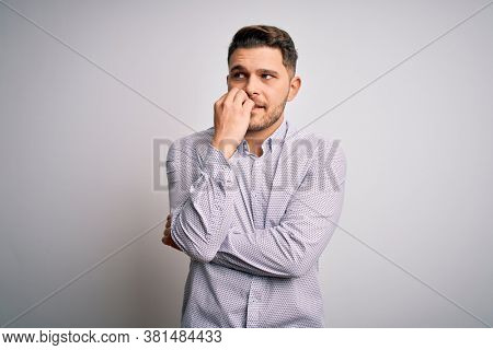 Young business man with blue eyes standing over isolated background looking stressed and nervous with hands on mouth biting nails. Anxiety problem.