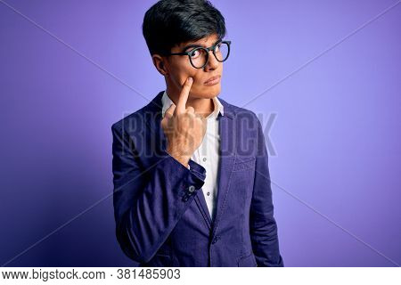 Young handsome business man wearing jacket and glasses over isolated purple background Pointing to the eye watching you gesture, suspicious expression