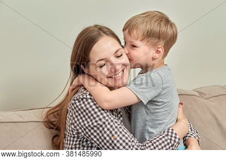 Mom And Son Together On The Couch. Boy Kisses His Beloved Mother On The Cheek.