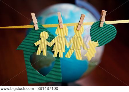 Paper Figures Of People, Family, House, Heart Hang On Ribbon On Clothespins On Background Of Globe.