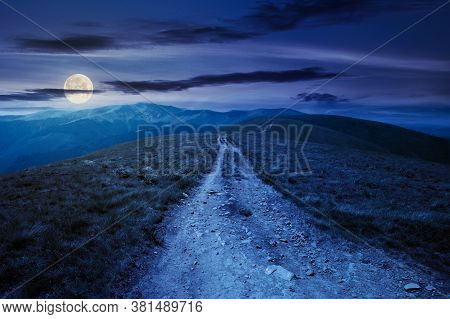 Mountain Road Through Grassy Meadow At Night. Wonderful Summer Adventure In Full Moon Light. Clouds