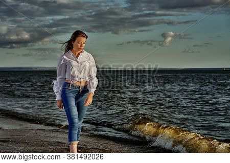 Young Brunette Woman Walks Along The Sandy Shore On A Sunny Summer Evening.